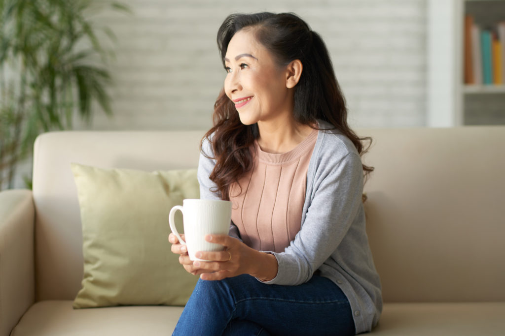 Smiling mature woman sitting on sofa and drinking coffee